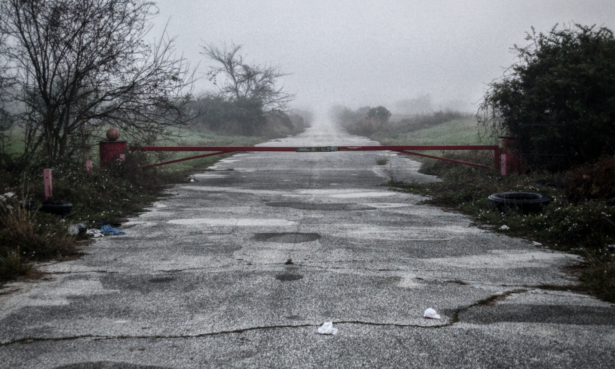 A blocked, disused road stretching off into the foggy distance.