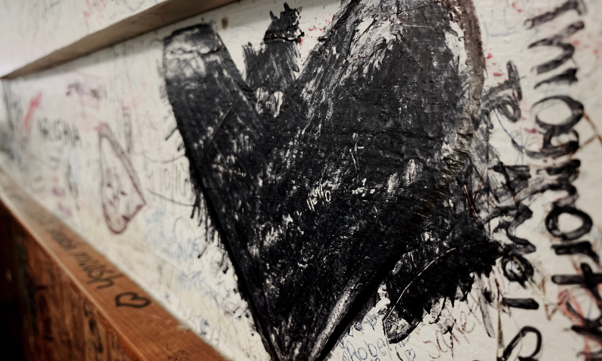 Black heart graffiti on wall at local pizzeria.