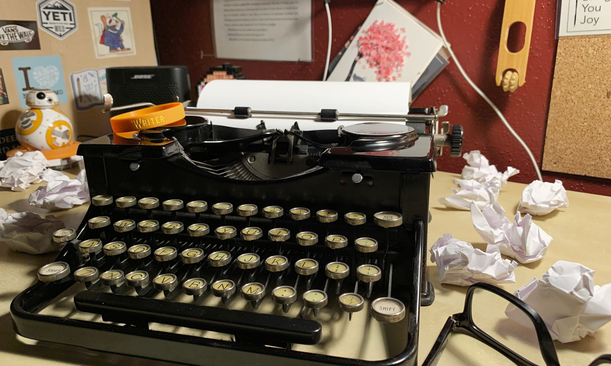 1934 Royal typewriter with glasses resting next to it surrounded by crumpled up paper.