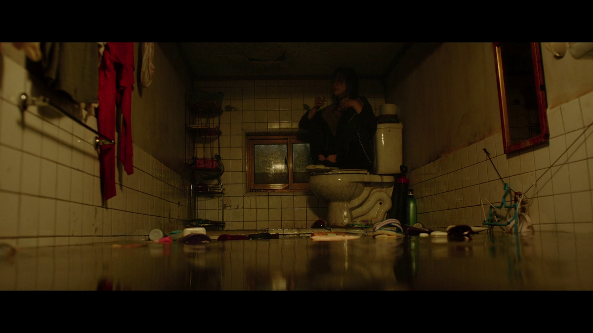 Ki-jung sitting on the toilet surrounded by a sea of sewage.