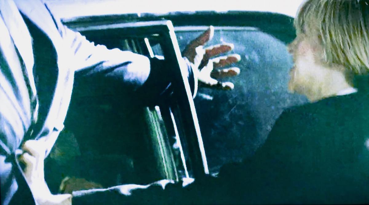 Billie Blake slamming a goon's arm in a car door.