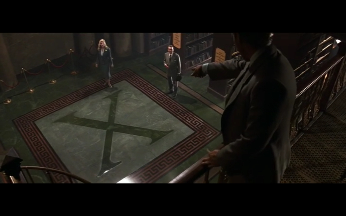 Indiana Jones pointing to a big X on the floor.