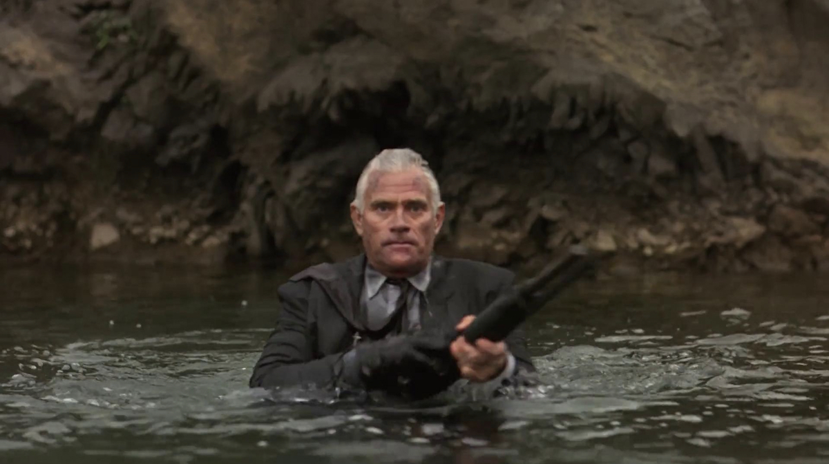 Farnsworth, up to his armpits in water, looking disturbed as he reloads his shotgun.