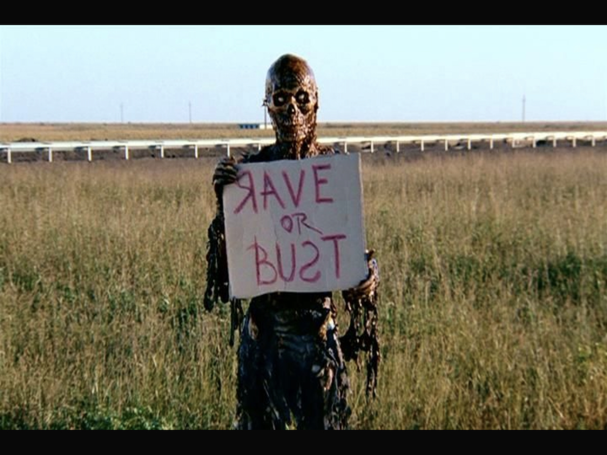 Zombie hitchhiking with a sign that reads: Rave or Bust (with the R in rave and S in bust written backwards).